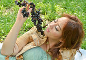Beautiful woman eat fruit in the park — Stock Photo