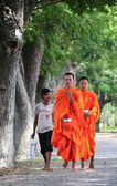 Asian young monks walking morning alms — Stock Photo
