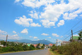 Mountain road at rainy day with clouds — Stock Photo