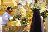 Buddhist devotees bathing Buddha statues at Shwedagon Pagoda — Stock Photo