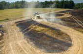 Tractor harrowing the field in fire — Stock Photo