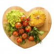 Vegetables on wooden board in a heart shape — Stock Photo #67107427