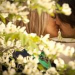 Couple kisssing behind dogwood flowers — Stock Photo #62906233
