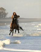 Woman riding wild horse on beach — Stock Photo
