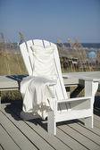 Wedding dress draped over beach chair — Stock Photo