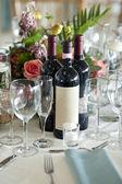 Elegant place setting with wine bottles — Stock Photo