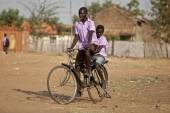 Students riding bike in Africa — Stock Photo