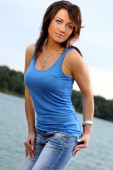 Pretty young woman posing in jeans and blue shirt — Stock Photo