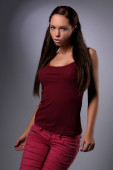 Sexy busty young girl posing in a red shirt  and a jeans — Stock Photo