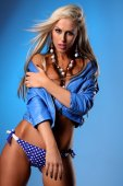 Sexy busty blonde young woman posing in blue leather jacket — Stock Photo