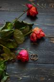 Wilting roses and wedding rings — Stock Photo