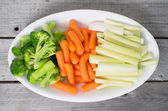 Vegetable tray with celery, broccoli, carrots on a wooden table — Stock Photo