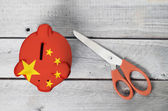 China cutting cost with a piggy bank overlaid by Chinese flag — Foto Stock