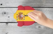 Spain saving concept with little hand dropping a coin into piggy — Stock Photo