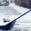 Big snow shovel full of heavy icy snow in front of house entranc — Stock Photo #63434365