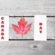 Concept Canada Day with red maple leaf on vintage wooden table — Stock Photo #64936695