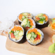 Set of vegetarian sushi rolls on a wooden plate isolated on whit — Stock Photo #76297157