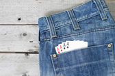 Four aces in blue jeans back pocket against wooden background — Stockfoto