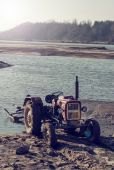 Old tractor on the river Vistula — Stock Photo