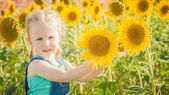 Beautiful girl plays with the sunflowers in a summer day — Stock Photo