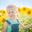 Beautiful girl plays with the sunflowers in a summer day — Stock Photo #52452171