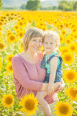 Mom with daughter in between beautiful sunflowers in summer day. — Stock Photo