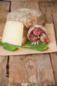 Queijo pecorino com lingüiça de javali e uma folha de figo sobre uma madeira — Foto Stock