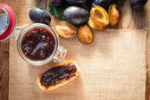 Plum jam on toasted bread with plums in the background — 图库照片