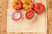 Tomatoes and tomato sauce, tomato puree on a wooden rustic table — Stock Photo