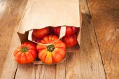 Tomatoes falling out of a paper bag on wooden rustic table — Stock Photo