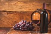 Red grapes and a bottle of wine and barrel on wooden rustic tabl — Stock Photo