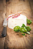 Smelly blue cheese on a wooden rustic table with green olives — Stock Photo