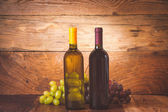 Red and white wine bottle with grapes and barrel on wooden rusti — Stock Photo