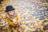 Little girl plays with yellow leaves in autumn sunshine. — Stockfoto