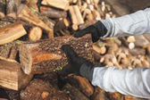 Leña en un pedazo de madera almacenada en la pila, manos sosteniendo una — Foto de Stock