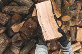 Firewood in a piece of wood stored on the stack, hands holding a — Stock Photo