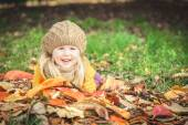 Beautiful girl, smiling blonde plays with the autumn leaves — Stock Photo