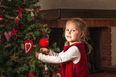 Beautiful little girl dressed in red, decorated Christmas tree. — Stock Photo