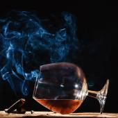 Glass of alcohol and smoking noble cigar on a black background — Stock Photo