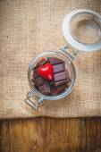 Chocolate and heart in a jar on a wooden background on the day o — Stock Photo