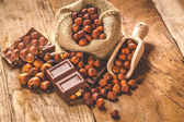 Milk chocolate with nuts on a wooden spoon in a country style. — Photo