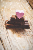 Pink heart on a black chocolate with rustic wooden background — Fotografia Stock