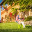 Little Girl and cat play on a green meadow in spring beautiful d — Stock Photo #71897777