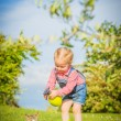 Little Girl and cat play on a green meadow in spring beautiful d — Stock Photo #71898239