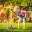 Little Girl and cat play on a green meadow in spring beautiful d — Stock Photo #71900055