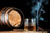 Glass of alcohol and smoking noble cigar on a black background — Стоковое фото