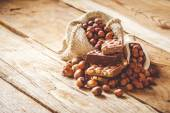 Milk chocolate with hazelnuts and walnuts in a sack on a wooden — Stock Photo