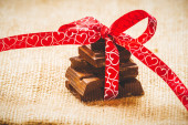 Chocolate with ribbon and heart on St. Valentine's day love. — Stock Photo