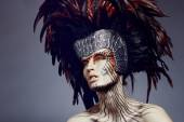 Woman with headwear and feathers — Stock Photo