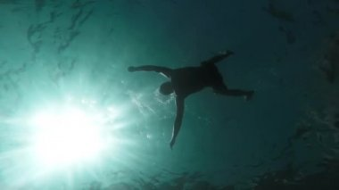 Silhouette Man Drowning Sinking Body In Deep Water Slow Motion Underwater Shot Ocean Murder Danger Lost At Sea Drown Death Lifeless Swimmer Sun Rays Waves Ripples Mortality Concept Gopro HD — Stock Video